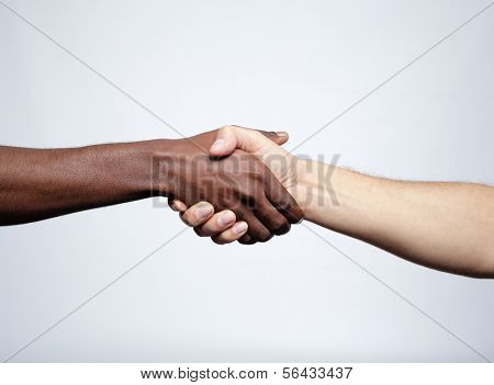 Handshake between african and a caucasian man over gray background