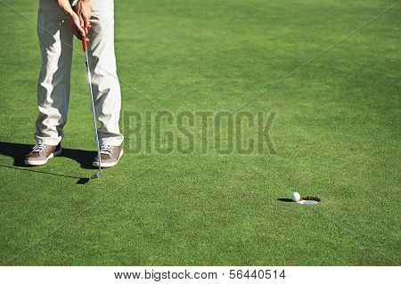 Golf man putting on green and aiming to sink golf putt shot on course poster