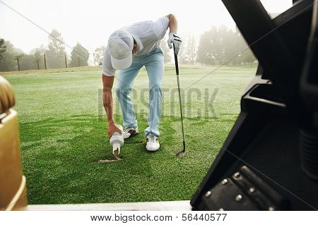 Golfer repairing divot by filling with sand on the fairway