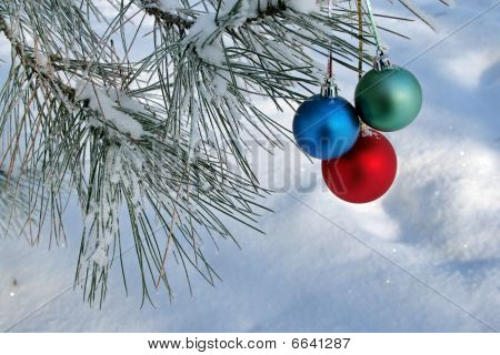 Three Balls On Pines Branch On Snow Background