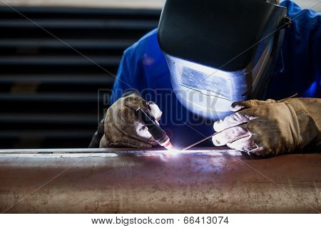 Welder in blue suit with proper protection