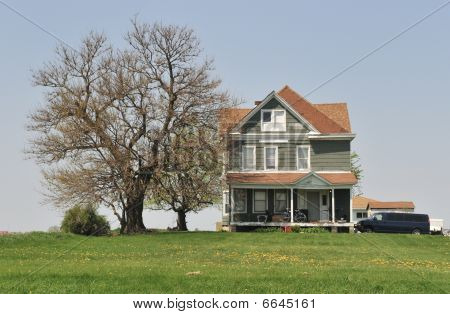 Midwestern farm house next to bare tree
