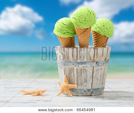 Three minty ice creams in rustic bucket at the seaside
