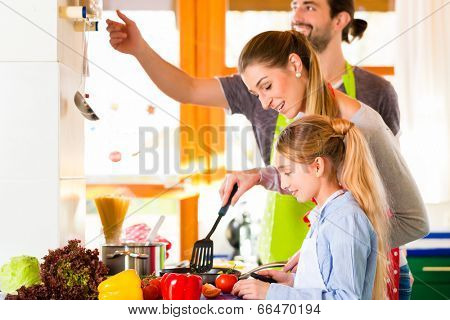 Family - Parents and child -preparing healthy meal in domestic kitchen