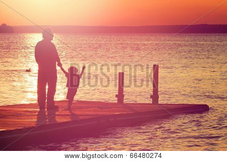 Father and son walking out on a dock at sunset poster