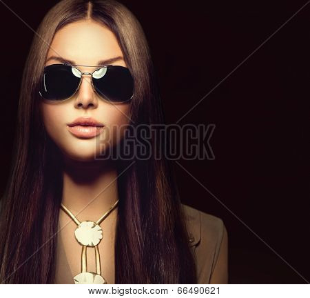 Beauty Fashion model girl with long brown hair wearing stylish sunglasses. Sexy woman portrait over black background