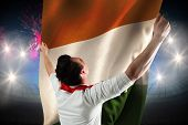 Excited football fan cheering against fireworks exploding over football stadium and ivory coast flag poster