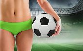 Fit girl in green bikini holding football against misty football stadium under spotlights poster