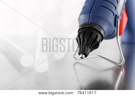 Dark blue glue gun and silicone stick on light background