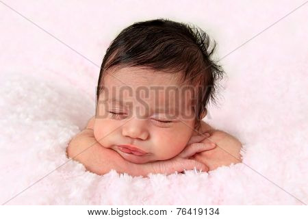 Newborn baby girl of Caucasian and Asian heritage wearing a knitted hat.