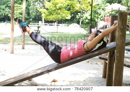 Sporty woman doing reverse crunches in outdoor park.