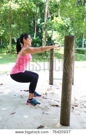 Beautiful strong woman doing squat exercise by the exercise bar in the park