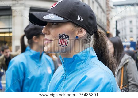 LONDON UK - SEPTEMBER 27: Profile portrait of beautiful girl with NFL logo painted on cheek. September 27 2014 in London. The street was closed to traffic to host NFL related games and events.