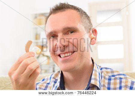 Man showing deaf aid in ear