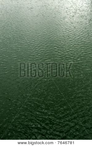 Waves reflect daylight on water surface of a river. poster