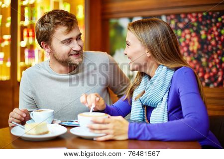 Young cheerful couple talking in cafe by cup of coffee