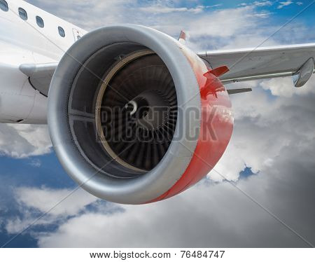Airplane With Red Engine Flying In The Clouds