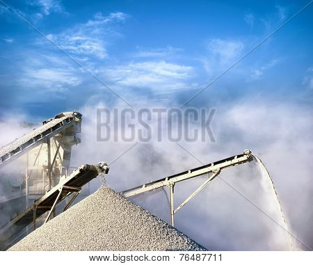 Stone crushing equipment, working conveyor loading gravel and producing air pollution with dust and smog