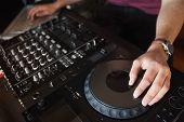 Close up of hands spinning the decks at the nightclub poster