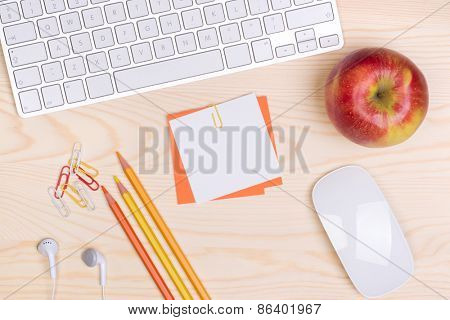 Desk with keyboard, notepaper and an apple, top view