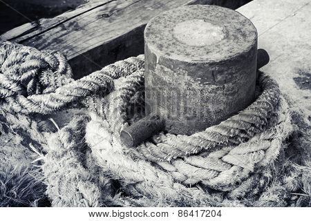 Old rusted mooring bollard with naval ropes on the pier black and white photo poster