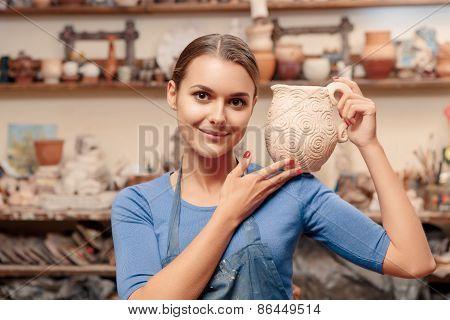 Girl holds a clay jar