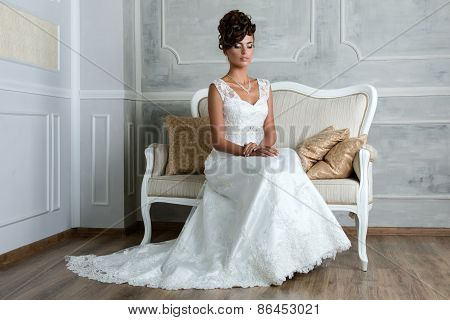 Young Luxurious Brunette Bride Sitting On Vintage Sofa