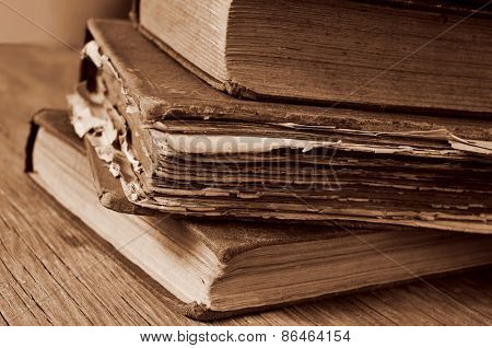 closeup of a pile of worn-out old books on a rustic wooden table, in sepia toning