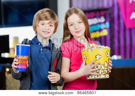 Portrait of cute brother and sister holding snacks against cinema concession stand