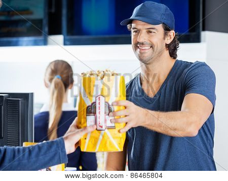 Happy male seller selling popcorn to man at cinema concession stand with colleague in background