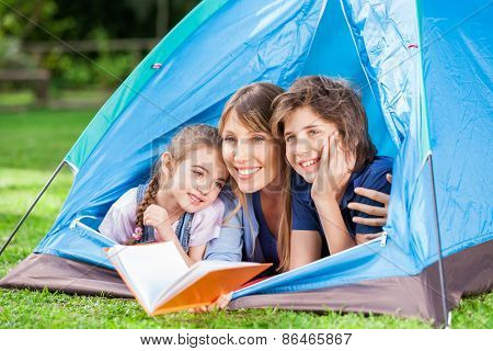 Happy children with mother holding book in tent at park