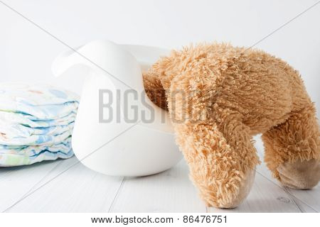 Teddy bear's head stuck in the potty - conceptual image representing potty training in young age troubles. poster