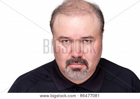 Dour angry middle-aged man glowering at the camera from under his brows head and shoulders isolated on white poster