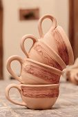 Beautiful clay cups. Life still of the perfectly made clay cups with tiny ornament set in figures on the pottery wooden table poster