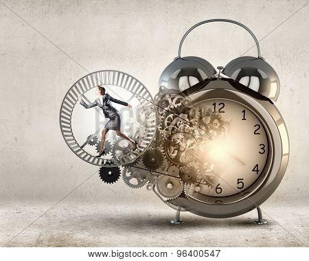 Young businesswoman running in wheel of gears mechanism
