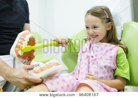 Girl In Dentists Chair Toothbrushing A Model