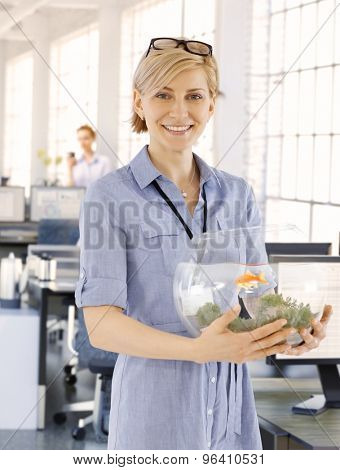 Blonde businesswoman holding small fishbowl in hand with a small goldfish, smiling.