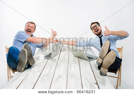 The two smiling businessmen with legs over table