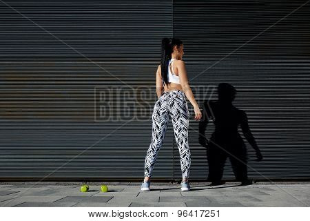 Woman with perfect figure and buttocks taking break against wall with copy space for your text