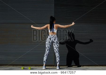 Rear view sporty female in sportswear exercising on black background with copy space for your text