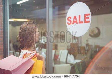 Smiling woman with shopping bags looking at window at the shopping mall