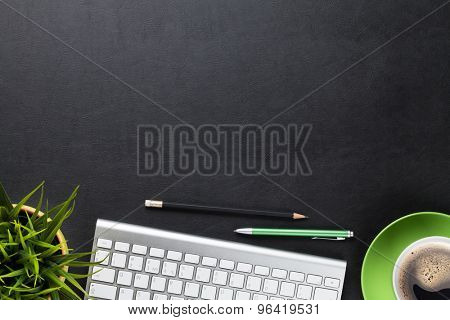 Office leather desk table with computer, flower and coffee cup. Top view with copy space