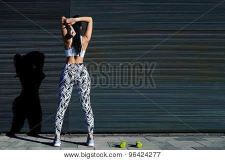 Young sporty woman with perfect figure and buttocks stretching her arms against wall with copy space