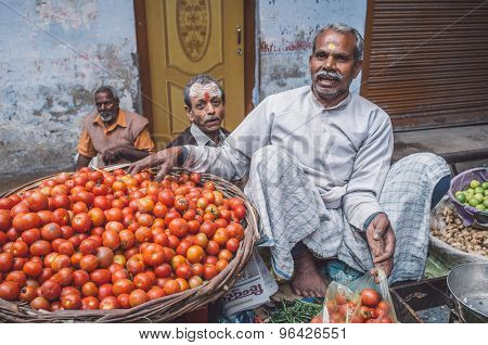 VARANASI, INDIA - 20 FEBRUARY 2015: Grocer puts tomatoes from basket into plastic bag for customer on street market. Post-processed with grain, texture and colour effect.