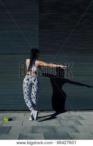 Athletic woman with perfect figure and buttocks shape exercising against wall with copy space