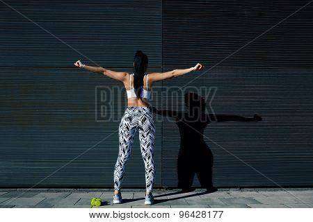 Back view portrait sporty woman with perfect figure and buttocks stretching her arms against wall