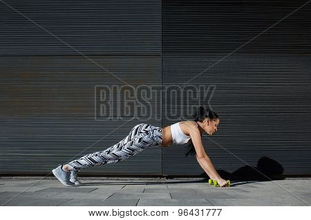 Healthy young female in workout gear doing push-ups on black background outdoors