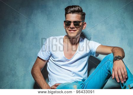 Handsome young man sitting while leaning on a wall, smiling to the camera.
