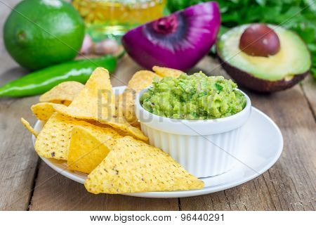 Cup With Chunky Guacamole Served With Nachos And Ingredients On Backgroung