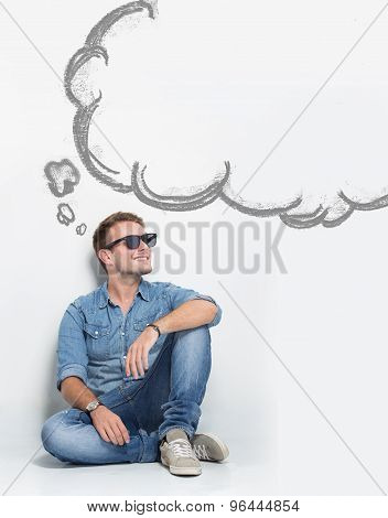 Young Caucasian Man Wear Sunglasses While Sitting On The Floor Thinking About Something